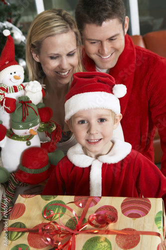 Boy 5-6 holding present in front of parents