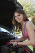 Young woman with jumper cables by car