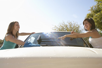 Two young women washing car