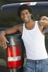 Young man holding car key standing by pick up truck, portrait