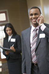 Business man using mobile phone with business woman writing in diary in background