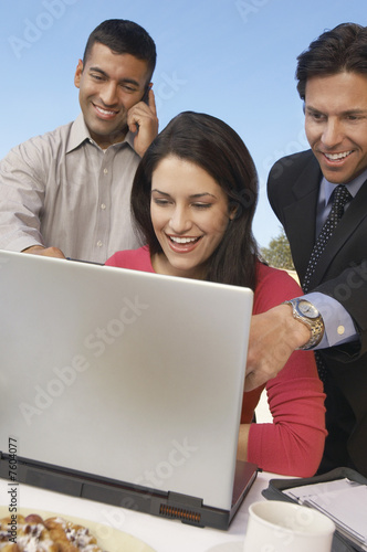 Three business people in front of laptop