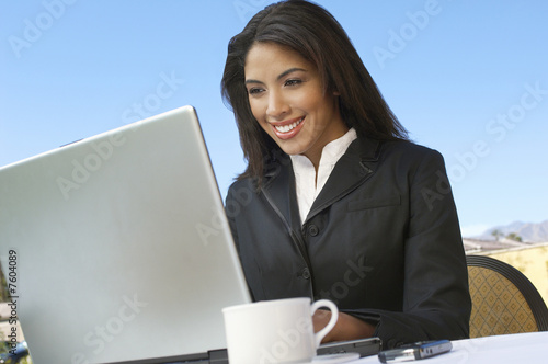Mid adult woman working on laptop outdoors