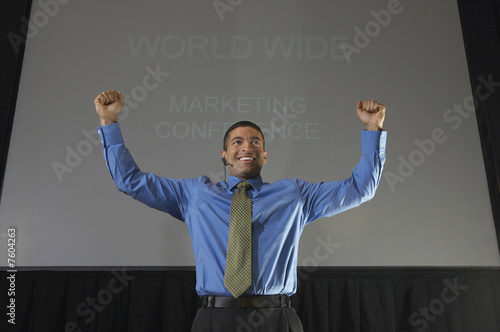 Business man speaking at conference, arms raised