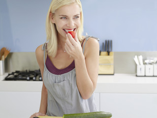 Smiling, young woman Snacking on cherry tomato in Kitchen