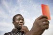 Soccer referee holding out red card and blowing whistle, portrait
