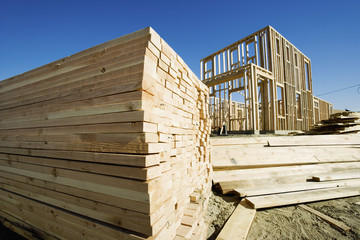 Stack of lumber, frame of house under construction