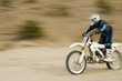 Motocross racer travelling at speed, outdoors