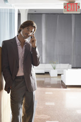 Businessman using mobile phone in lobby