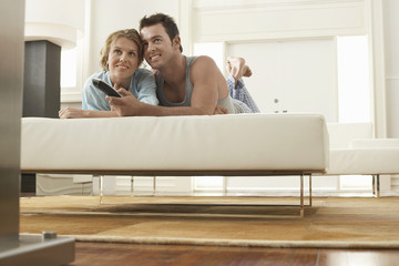 Couple Lying on Sofa Watching Television