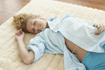 Woman Lying on Bed Listening to iPod
