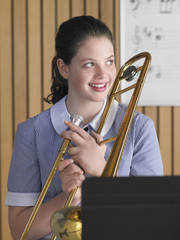 High school girl holding trombone in class, portrait