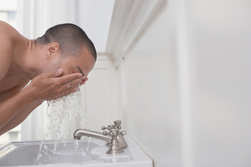 Man washing face in bathroom sink