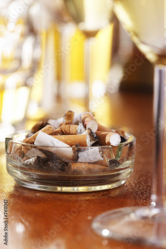 Full ashtray on table with glasses of wine