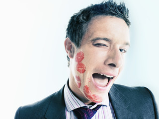 Businessman with lipstick kiss-marks, winking