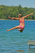 Young Girl Jumps Off Dock into Lake Extending Arms and One Leg