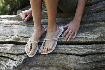 Teenage girl 16-17 years wearing flip-flops sitting on tree trunk, low section