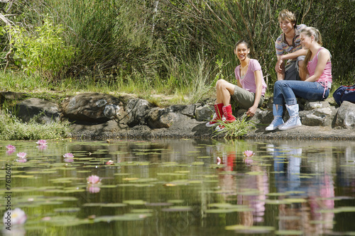 Teenage girls and boy 16-17 years sitting on stones by lake, smiling