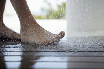 Woman standing under outdoor shower, close up of feet, low section,