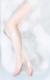 Woman legs in bath with foam poster