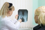 Doctor and patient examine x-ray of hands poster