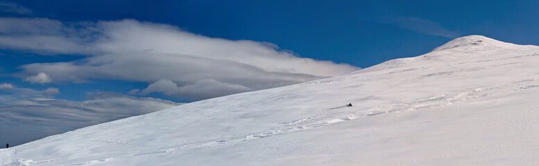 Snowy white mountain slope with blue sky panorama