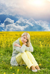 Beautiful young woman sitting in a flower field