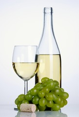 Bottle and glass of white wine with grapes and cork