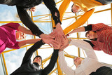 Six friends joining hands low angle view poster
