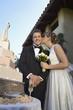 Bride kissing groom near wedding cake, portrait