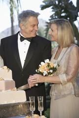Middle-aged couple cutting wedding cake, portrait