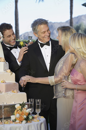 Middle-aged couple with young man and woman gathered near wedding cake