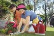 Two women planting flowers in garden