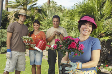 Four people gardening, focus on woman with flower in foreground