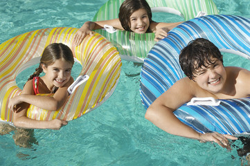 Three children in inflatable rafts in swimming pool, portrait