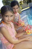 Girls drinking juice from crazy straws on edge of swimming pool, portrait