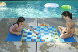 Two girls playing on large draughts board beside swimming pool