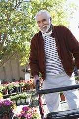 Elderly man with walking frame in garden center