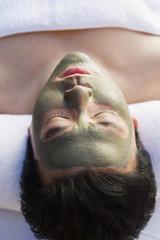 Young woman wearing mud facial mask at health spa, close-up