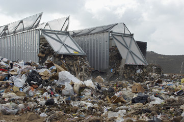 Trucks dumping waste at landfill site