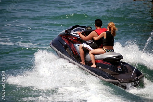 Staande foto Water Motorsp. Young Couple on a Black Jetski