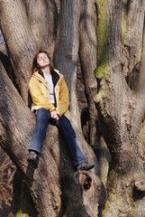Young woman sitting on tree and relaxing