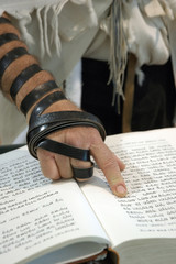 Jewish man and prayer book with phylacteries and talit