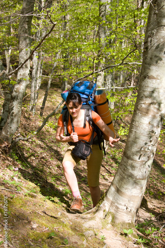 hiker girl with backpack traveling in spring forest