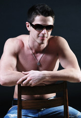 Naked muscular young man in glasess at black background