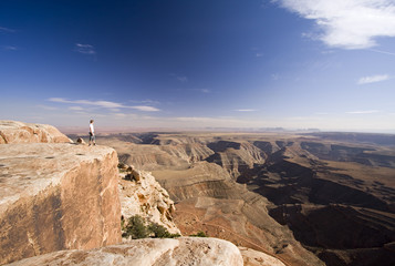 man standing on cliff edge at Muley Point, Utah