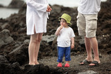 Little boy on lava beach together with parents poster