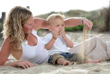 young beautiful mommy playing with her baby son on the beach poster