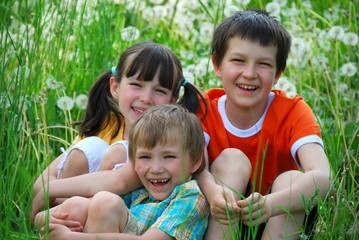 Smiling kids in grassy field