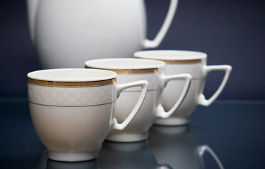 Four white cups on blue
